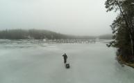<h5>Ensijäillä kävelyä</h5><p>Nuuksiossa oleva pieni järvi. Mies vetää ahkiota mukanaan kalastusvehkeitä. Tunnus: GO032902</p>