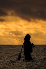 <h5>Siluetti kahlaavasta kalamiehestä</h5><p>Mies kahlaa matalassa rantavedessä   etsien kala-apajaa. Tunnus: 7336</p>